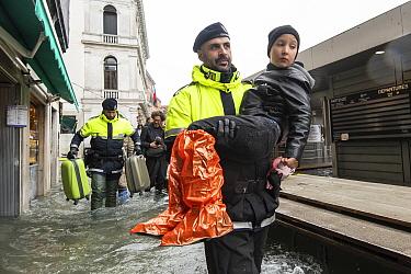 Venetian police carrying boy through flooding in Venice, Italy, December 2019.