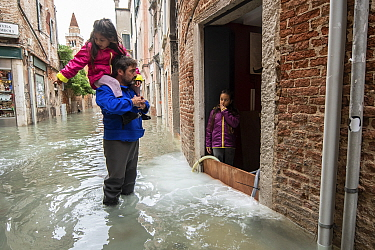 Man carrying child on shoulders during flooding in Venice, Italy, December 2019.
