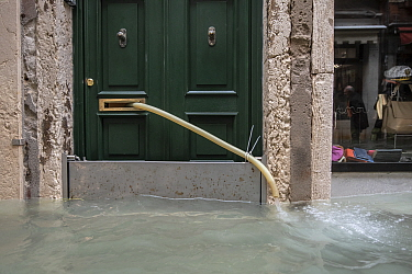 Pipe pumping out water from house during flooding in Venice, Italy, December 2019.
