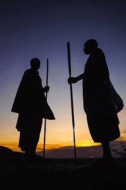 Masaai warriors, two silhouetted in ceremonial dance at dusk. Ngorongoro Conservation Area, Serengeti National Park, Tanzania. March 2014.