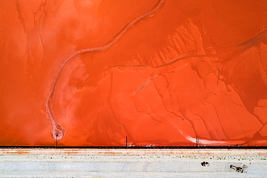 Bulldozers on red mud dam, shoring up the dam to prevent dangerous leaks.  These Red mud deposits in storage pond are a highly alkaline waste product produced by the industrial production of alumini...