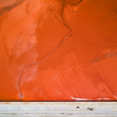 Bulldozers on red mud dam, shoring up the dam to prevent dangerous. leaks  These Red mud deposits in storage pond are a highly alkaline waste product produced by the industrial production of alumini...