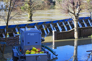 Water pump with flood barrier beyond holding back flooded River Severn. After Storm Ciara and Storm Dennis, the wettest February recorded in the UK. Ironbridge, Shropshire, England, UK. February 2020.