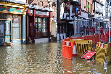 Shops and street in River Severn floodwaters, group of people taking photographs in background. After Storm Ciara and Storm Dennis, the wettest February recorded in the UK. Shrewsbury, Shropshire, Eng...