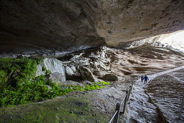 Tourists walking into cave. Milodon Cave Natural Monument, Magallanes, Chile. January 2020.