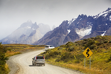 Cars on winding road through mountains. Torres del Paine National Park, Patagonia, Chile. January 2020.