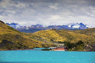 Pehoe Lodge on shore of Lake Pehoe, mountains beyond. Lake turquoise coloured due to glacial rock flour. Torres del Paine National Park, Patagonia, Chile. January 2020.