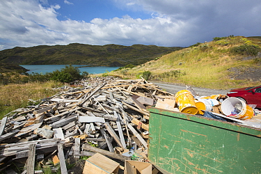 Skip and pile of rubbish from a tourist lodge, Lake Pehoe in background. Torres del Paine National Park, Patagonia, Chile. January 2020.