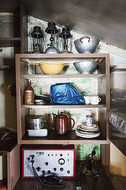 Radio, kitchen crockery and colanders on shelf in Wordie House, a former British scientific research base. Winter Island, Argentine Islands, Antarctica. 2020.