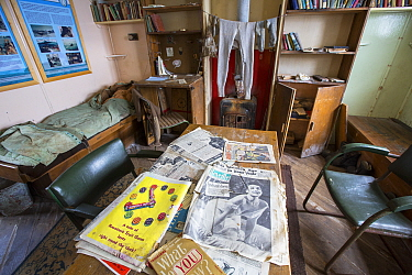 Magazines on table and clothes drying over stove in Station W, a former British scientific research station evacuated in 1959. Detaille Island, Graham Land, Antarctica. 2020.