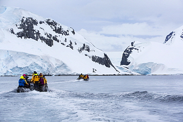 Tourists from expedition cruise ship in zodiacs heading towards mountains of Spert Island, Palmer Achipelago, Antarctica. December 2019.