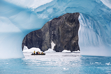 Tourists from expedition cruise ship in zodiac between ice arch and rock cliff on Spert Island. Palmer Archipelago, Antarctica. December 2019.