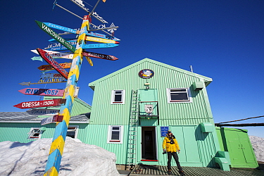 Man outside Vernadsky Station Ukrainian research base, signpost pointing to places across the world. Galindez Island, Argentine Islands, Antarctica. December 2019.
