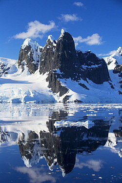 Mountain peaks and glaciers reflected in Lemaire Channel between Booth Island and the Kiev Peninsula, Antarctica. December 2019.