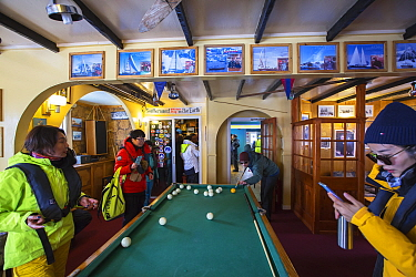 Tourists from expedition cruise ship playing at billiards table and purchasing postcards in shop. Vernadsky Station Ukranian research base, Galindez Island, Argentine Islands, Antarctica. 2019.