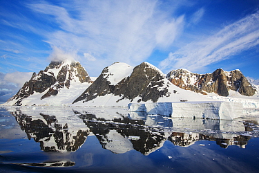 Snow covered peaks of Booth Island and sky reflected in Lemaire Channel, Antarctica. December 2019.