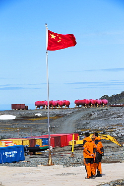 Workers standing near Chinese flag at Great Wall Station, Chinese research base, King George Island, South Shetland Islands, Antarctica. January 2020.
