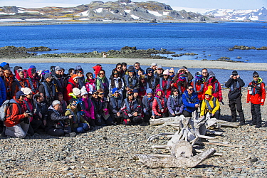 Chinese tourists posing beside Whale skeleton at Great Wall Station, a Chinese research base. King George Island, South Shetland Islands, Antarctica. January 2020.
