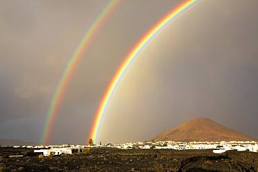 Double rainbow over town and volcano. Near Arrecife, Lanzarote, Canary Islands, Spain. November 2019.
