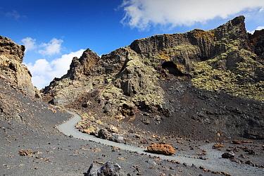 Footpath through volcanic soil and rocks inside Caldera de Los Cuervos volcano. Lanzarote, Canary Islands, Spain. November 2019.