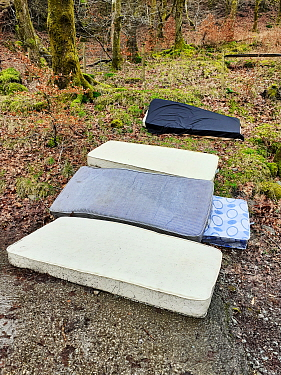 Mattreses fly tipped and illegally dumped in car park. White Moss, near Ambleside, Lake District National Park, England, UK. February 2020.