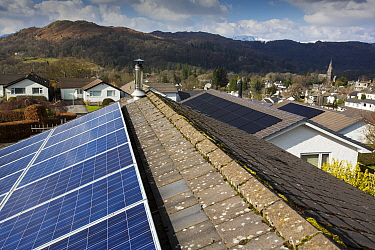 Photovoltaics on roofs of bungalows, hills in background. Ambleside, Lake District National Park, Cumbria, England, UK. March 2020.