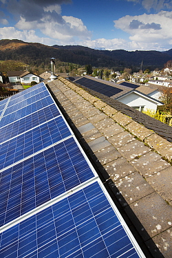 Photovoltaics on roofs of houses, hills in background. Ambleside, Lake District National Park, Cumbria, England, UK. March 2020.