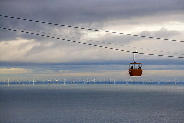 Tourists in cable car traveling between Llandudno and Great Orme summit, windfarm in Irish Sea in background. Wales, UK. October 2018.