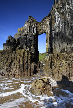 Rock arch at Skrinkle, vertical beds of carboniferous age limestone. Near Tenby, Pembrokeshire, Wales, UK. May 2019.
