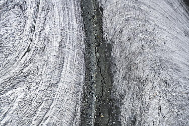 Medial moraine between two glaciers, the slight difference in speed of the glaciers results in curved drag patterns in the ice, aerial view. Lower Theodul Glacier, Zermatt, Valais, Switzerland. Septem...