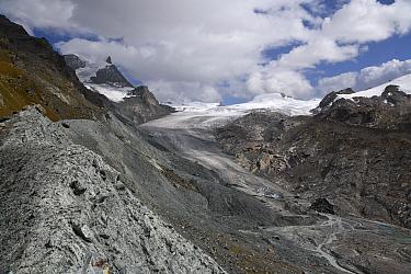 Lateral moraine deposit at edge of Findel Glacier. Glacier in retreat with braided stream below. Zermatt, Valais, Switzerland. September 2019.