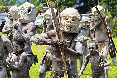 Mudmen, Papuan men in traditional clay masks, bodies painted with clay, boys also painted. At Sing-sing gathering where traditional cultures including dance and music are shared. Morobe Show, Lae, Pap...
