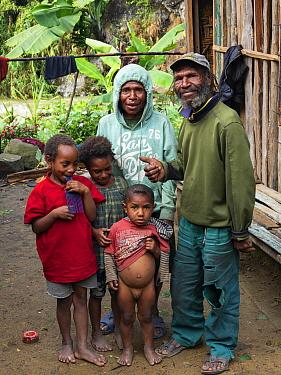 Papuan family beside house, portrait. Koronige River in background. Bogo, Kerowagi District, Simbu Province, Papua New Guinea. 2019.