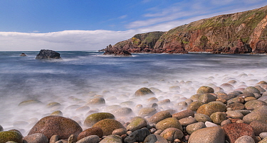 Pebbles on shoreline, cliffs along coast beyond. Bloody Foreland, Knockfola, County Donegal, Ireland. June 2020.