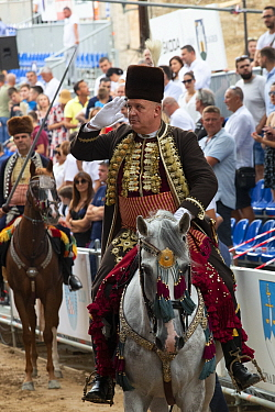 Man on horseback saluting during Alka procession, spectators in background. Held on the first Sunday in August since 1715 the Alka commemorates the victory of Christians over Ottoman Turks. Inscribed...