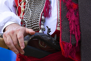 Man in traditional dress holding gun during Alka commemorations, close up. Held on the first Sunday in August since 1715 the Alka commemorates the victory of Christians over Ottoman Turks. Inscribed o...