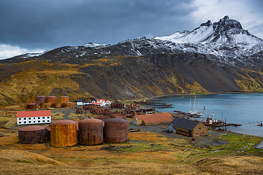 Vats and buildings of abandoned whaling station with mountains above. Grytviken was the largest whaling station on South Georgia. October 2017.