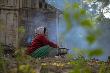 Local elderly woman cooking a meal from her family over open fire (with wood from local forest) Abor hills, Arunachal Pradesh, India, December 2019.  The locals are also known to construct their hou...