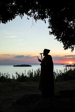 Priest standing beside Lake Tana at sunset. Mandaba Medhane Alhem Orthodox Monastery, near Gorgora, Ethiopia. 2018.
