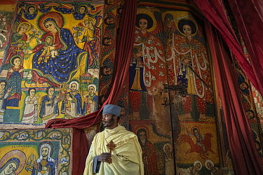 Young priest standing in front of mural paintings in the sanctum of Ura Kidane Mehret, an Ethiopian Orthodox Church. Zege Peninsula, Ethiopia. 2018.