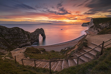 Durdle Door rock arch at sunset, coastline and Bats Head beyond. Dorset, England, UK. October 2020.