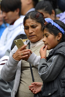 Children visiting Monarch butterfly reserve. Teacher and child looking at images of butterflies on mobile phone, Sierra Chincua Sanctuary, Mexico.