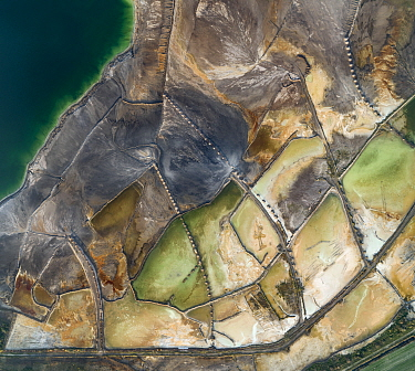 Aerial view of ash pond near Turek, Poland. Former open pit coal mine now used to store coal ash after burning in power plants. The ash is mixed with water and pumped through pipelines (fixed on sand...