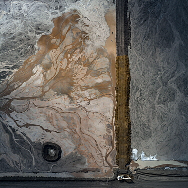 Bulldozer maintaining wall of an ash pond, East-Central Europe. After coal is burned in power plants, the waste ash is mixed with water and pumped through pipelines into sludgy lagoons commonly known...