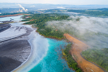 Aerial view of ash pond near coal power plant visible in the background, Bosnia and Herzegovina. After coal is burned in power plants, the waste ash is mixed with water and pumped through pipelines in...