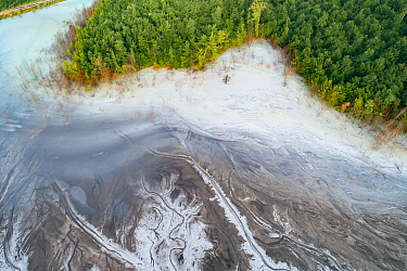 Aerial view of ash pond on the edge of a forest, Bosnia and Herzegovina. After coal is burned in power plants, the waste ash is mixed with water and pumped through pipelines into sludgy lagoons common...