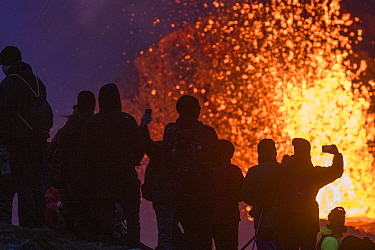 Group of tourists silhouetted against volcanic eruption, gathered at one of the viewing points close to the craters of the Fagradalsfjall volcano on Iceland. The best viewing points differ from day to...