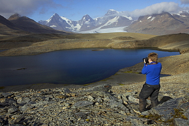 Russell Laman photographing Crean Lake on the hike between Fortuna Bay and Stromness, retracing part of Shackleton's route. South Georgia, February 2011. Model released.