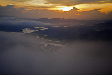 Aerial view of sunrise, low clouds and the Sarawaget Range - mountains of the Huon Peninsula, Papua New Guinea