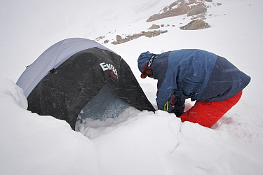 Skier Phil Atkinson digging out his tent after an all night blizzard at camp site in the upper Sky Top Lakes Valley near Granite Peak, Beartooth Mountains, Montana, USA. May 2008